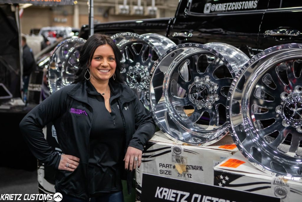 woman standing next to display of aftermarket wheels for sale at Motorama truck show