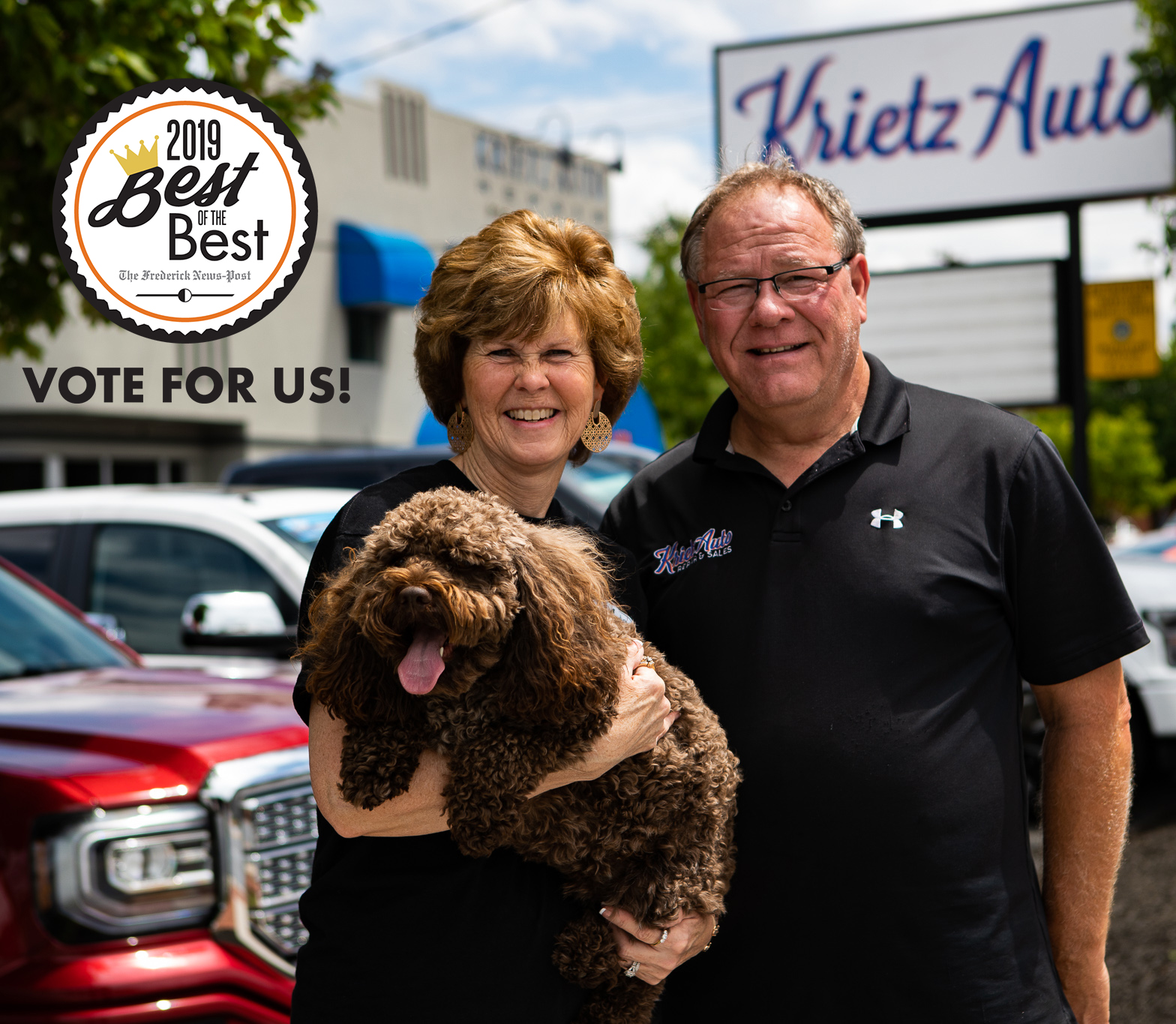 woman and man stand side by side in front of car dealership. woman holds brown dog